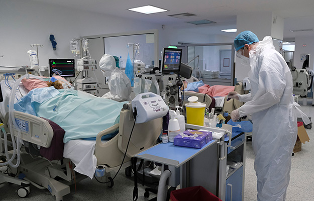 2 doctors in protecting suits watching over a covid patient | Epigenetics May Help Explain Why COVID-19 Becomes More Severe In Some Patients